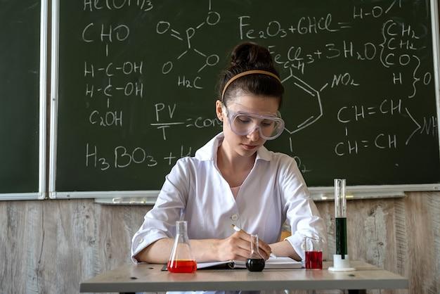 Vrouwelijke wetenschapper-leraar met bril in laboratoriumjas op zoek naar chemische vloeistoffen in kolven in klaslokaal tegen schoolbord