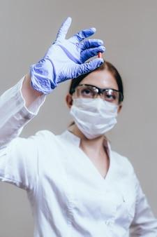 Vrouwelijke wetenschapper met beschermend masker toont een medicijnpil. nieuw innovatief behandelconcept. het concept voor gezondheid