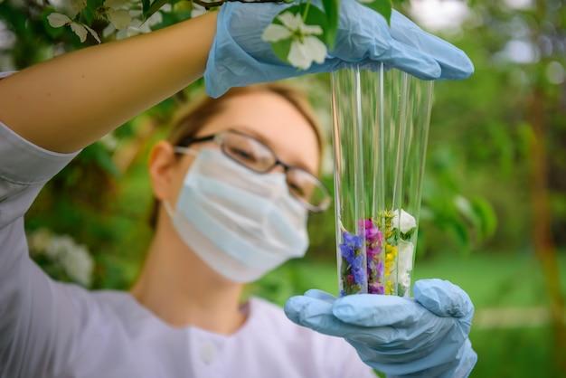 Vrouwelijke wetenschapper met bril, masker en handschoenen met reageerbuizen in haar handen bestudeert de eigenschappen van planten tegen bloeiende bomen.