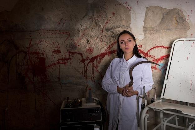 Vrouwelijke wetenschapper met grote ijzeren sikkel in kerker met bloedige muren in een halloween-horrorconcept