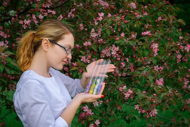 Vrouwelijke wetenschapper met reageerbuizen bestudeert de eigenschappen van planten in de botanische tuin, bloemengeuren, natuurlijke cosmetica, kruidengeneeskunde, parfums