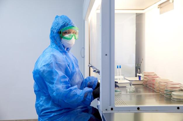 Vrouwelijke wetenschapsonderzoeker in beschermende uniform en apparatuur werkt met petrischaal in laboratorium