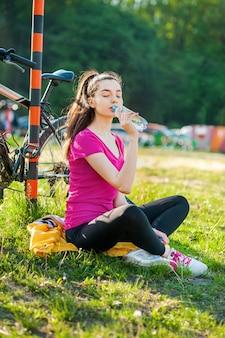 Vrouwelijke wielrenner, brunette meisje rusten en drinkwater