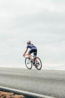 Vrouwelijke wielrenner fietsen de heuvel op