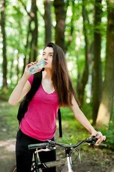 Vrouwelijke wielrenner in roze t-shirt op een fiets, met fles water, drank, sportvrouwen in het bos