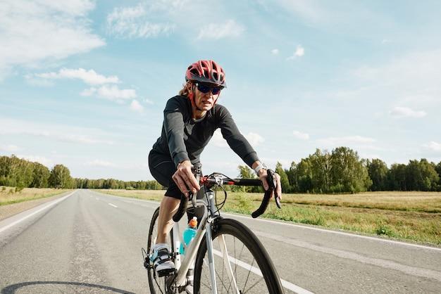 Vrouwelijke wielrenner in sportkleding die buiten op een racefiets op de weg rijdt