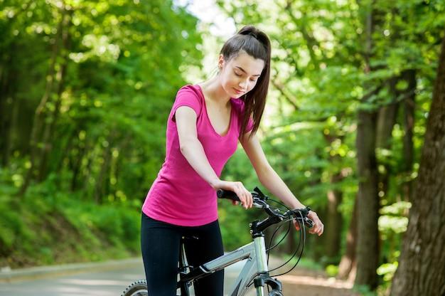 Vrouwelijke wielrenner op een fiets op asfaltweg in het bos