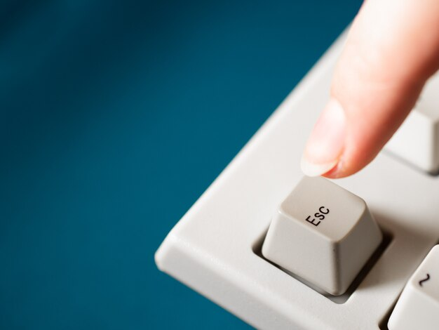 Vrouwelijke wijsvinger drukt op de esc-knop. detailopname