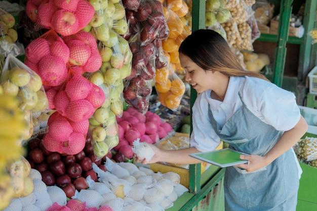 Vrouwelijke winkelbediende met behulp van digitale tablet