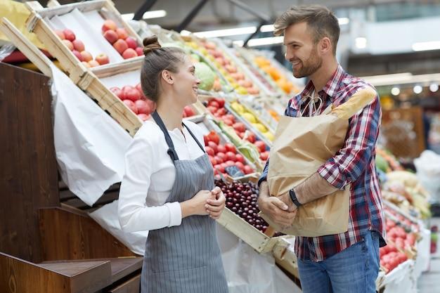 Vrouwelijke winkelbediende praten met klant