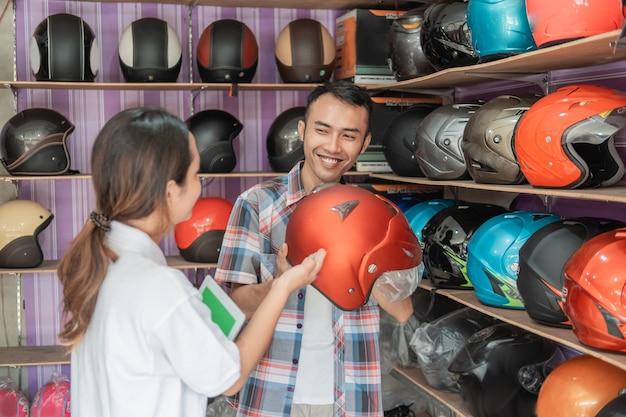 Vrouwelijke winkelbediende verkoopt helmen aan jonge mannen in een helmwinkel