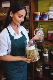 Vrouwelijke winkelier met een potje kruiden