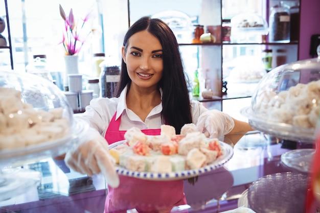 Vrouwelijke winkelier met lade van turkse zoetigheden aan balie