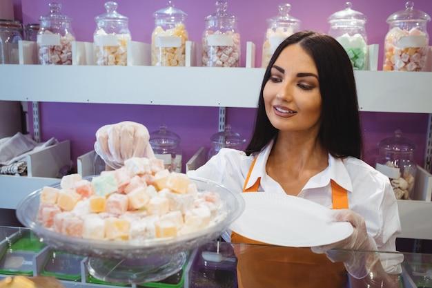 Vrouwelijke winkelier turkse gebakjes serveren in een bord aan balie