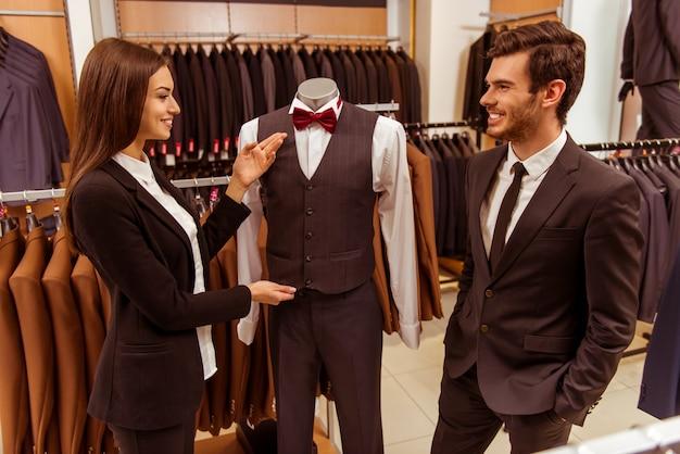 Vrouwelijke winkelmedewerker die en een kostuum glimlacht aanbiedt.