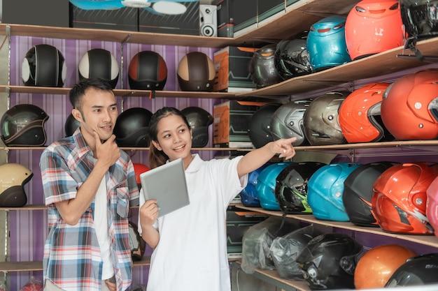 Vrouwelijke winkelmedewerkers maken reclame voor online winkels voor mannen die tablets gebruiken wanneer ze naar displayrekken in helmwinkels wijzen