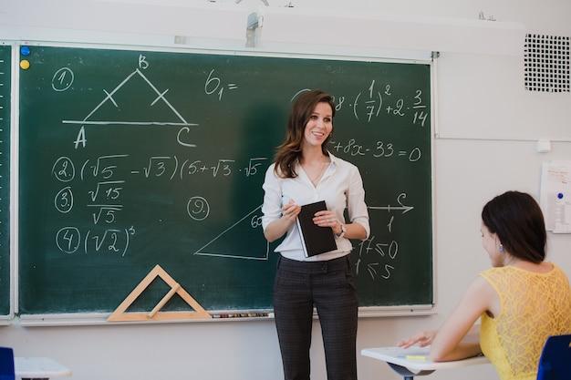 Vrouwelijke wiskundeleraar in interactie met haar jonge basisschoolleerlingen