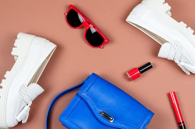 Vrouwelijke witte instappers, blauwe tas en rode platte accessoires liggen