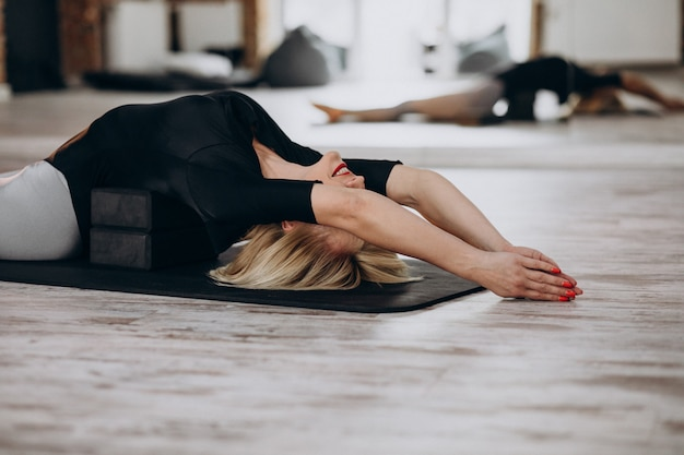 Vrouwelijke yoga-instructeur uitoefenen op de sportschool