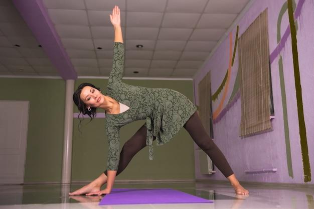 Vrouwelijke yoga presenteren yogamethoden in de sportschool