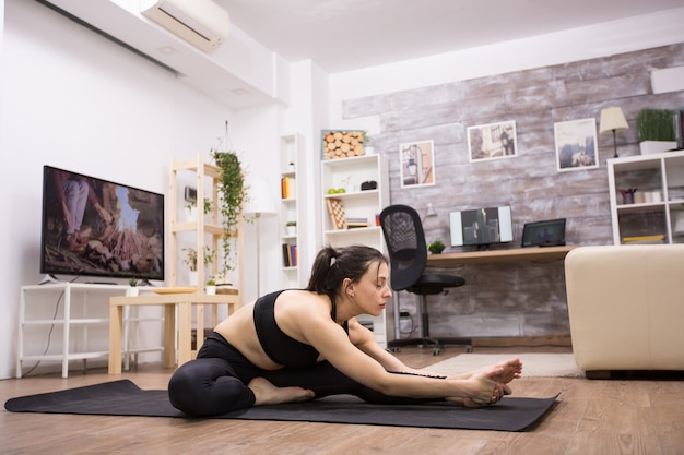 Vrouwelijke yogabeoefenaar die haar oefening thuis doet en zwarte sportkleding draagt.