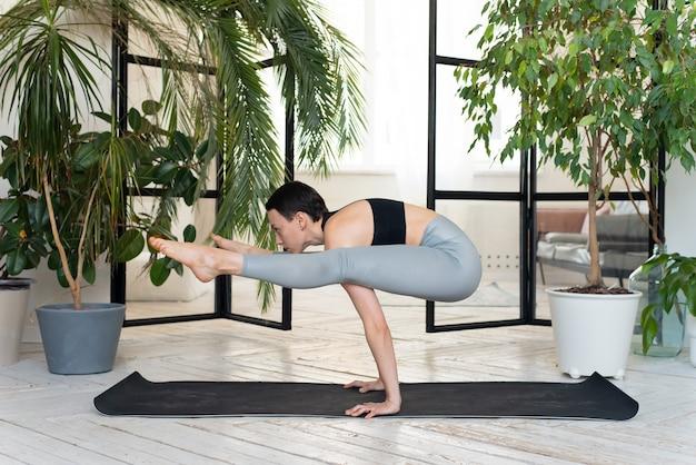 Vrouwelijke yogaleraar die in studio oefent. vrouw doet een handstand.