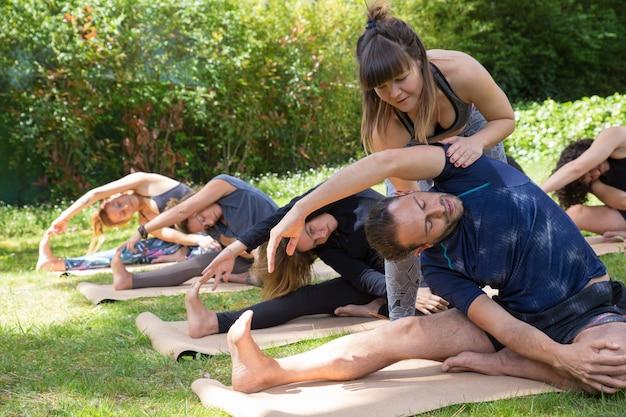 Vrouwelijke yogaleraar die stagiair helpt