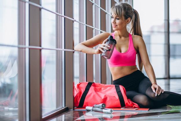 Vrouwelijke yogatrainer die telefoon met behulp van