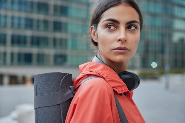 Vrouwelijke yogatrainer wacht op iemand op straat heeft een trainingspauze, herstelt de kracht na de training leidt een gezonde levensstijl staat zijwaarts tegen de wazige stad