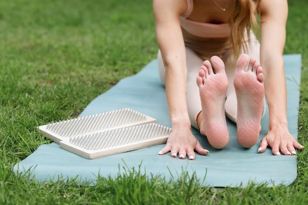 Vrouwelijke yogavoeten met deuken van een plank met spijkers op een groen gazon. yoga training