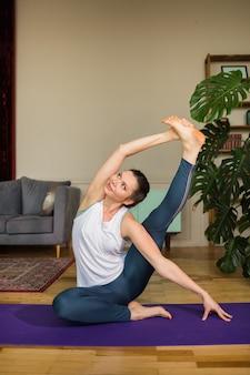 Vrouwelijke yogi in een sportuniform voert een asana uit op een mat in de kamer