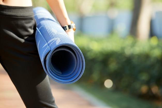 Vrouwelijke yogi met fitnessmat