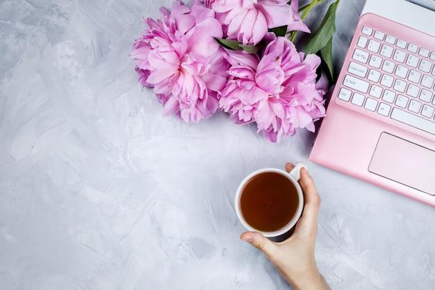 Vrouwelijke zakelijke mockup met roze laptop, pioenrozen boeket en vrouw hand met kopje warme thee
