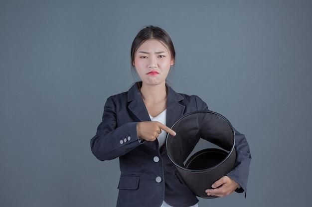 Vrouwelijke zaken met zwart afval die gebaren tonen