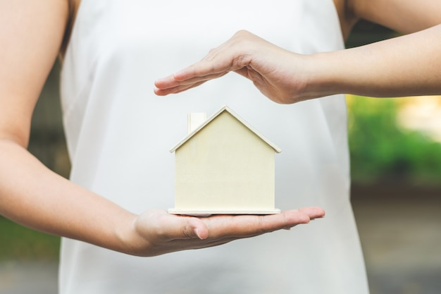 Vrouwelijke zakenlieden zetten het model thuis op de palm