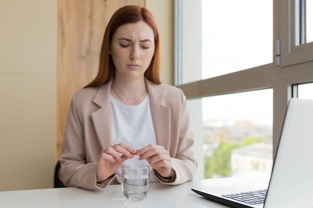 Vrouwelijke zakenman die aan laptop werkt, patiënt die medicijnpillen neemt met glas water