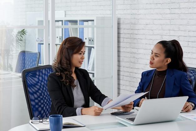 Vrouwelijke zakenpartners bespreken contractdetails voordat ze documenten ondertekenen tijdens vergadering