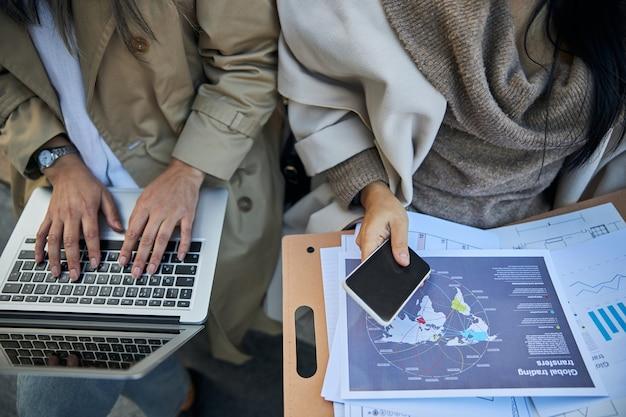 Vrouwelijke zakenpartners die moderne apparaten gebruiken en documenten bestuderen