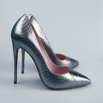 Vrouwelijke zilveren schoenen op grijze achtergrond