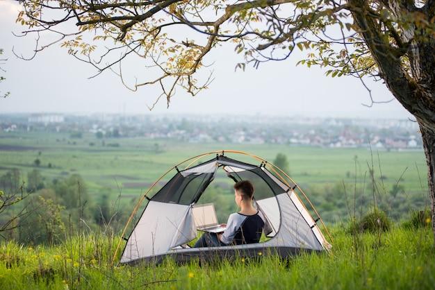 Vrouwelijke zitting in een tent bovenop een heuvel die haar laptop met behulp van terwijl het kamperen