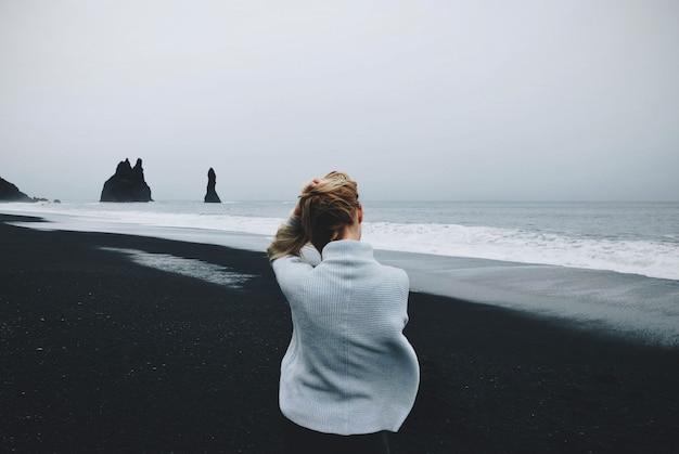 Vrouwelijke zitting op de kust dichtbij het water met een bewolkte erachter hemel op de achtergrond van