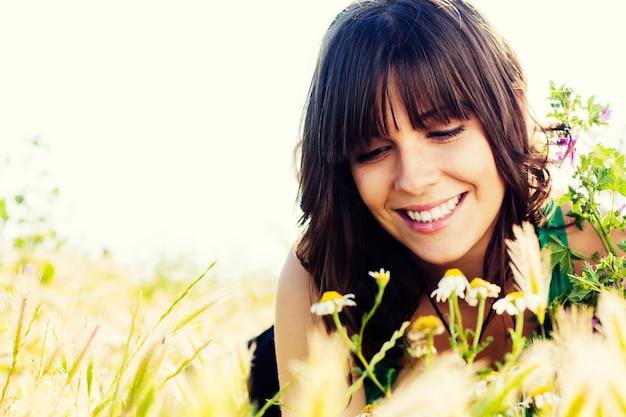 Vrouwelijke zitting op het veld en snuiven bloemen