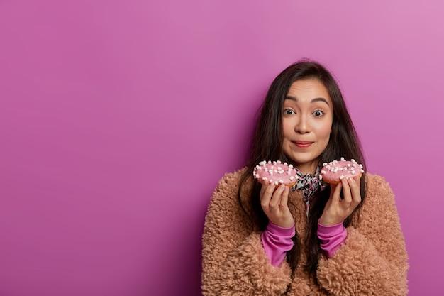 Vrouwelijke zoetekauw houdt lekkere geglazuurde gekleurde donuts vast, heeft suikerverslaving, wil nu een heerlijk dessert eten