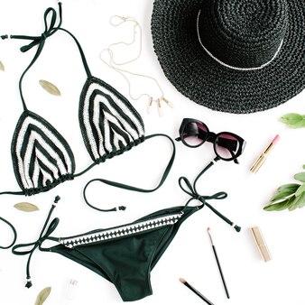 Vrouwelijke zomer bikini badpak accessoires collage op wit met hoed, groene takken, ketting en zonnebril.