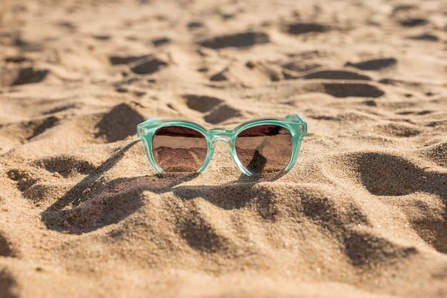 Vrouwelijke zonnebril op zand