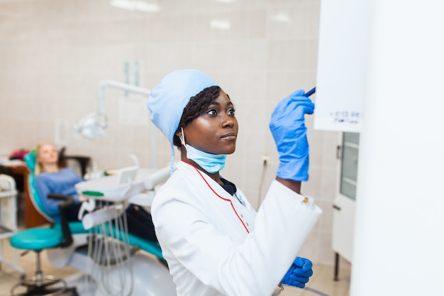 Vrouwelijke zwarte tandarts in tandartspraktijk die met vrouwelijke patiënt praat en zich voorbereidt op de behandeling, bestudeert een röntgenfoto. moderne medische apparatuur
