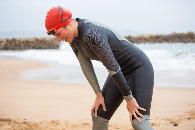 Vrouwelijke zwemmer die neer op strand kijkt