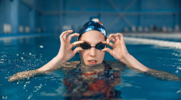 Vrouwelijke zwemmer in zwembroek, badmuts en bril poseert in het zwembad