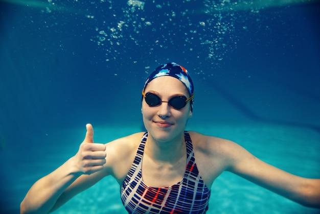 Vrouwelijke zwemmer in zwembroek, badmuts en bril toont duimen onder water in het zwembad