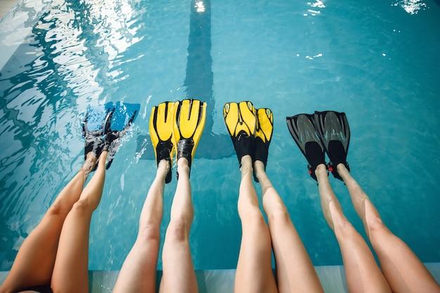 Vrouwelijke zwemmers groep bij het zwembad, voeten in flippers